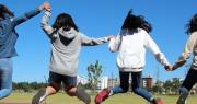 Ragazze che saltano per mano in un parco per bandi pon comune di bologna adolescenti e giovani