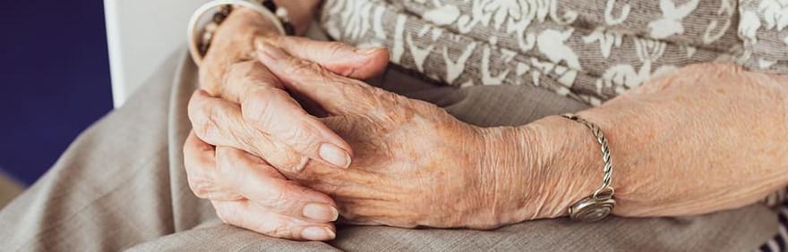 Mani di donna anziana intrecciate