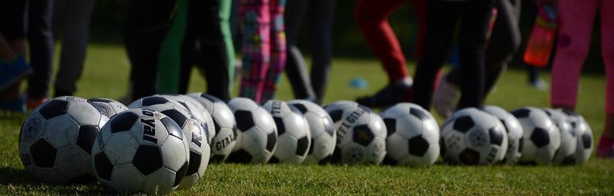 Foto di palloni da calcio su campo sportivo con piedi di calciatori